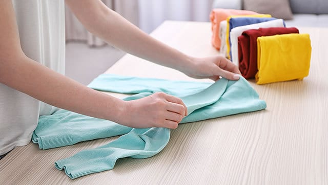 Girl folding washed clothes