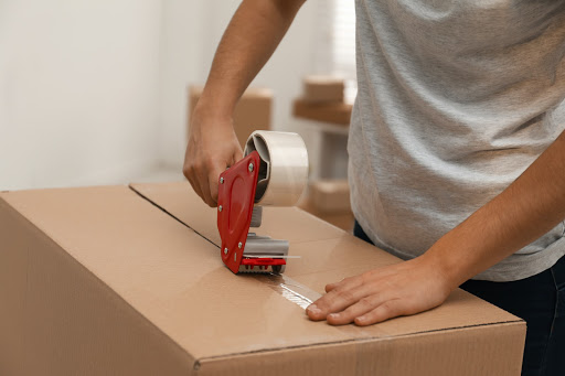 man packing boxes for house move