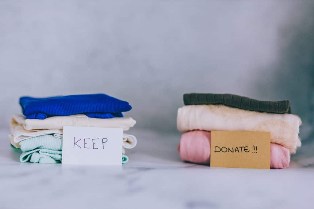 decluttering and sorting clothes into keep and donate piles